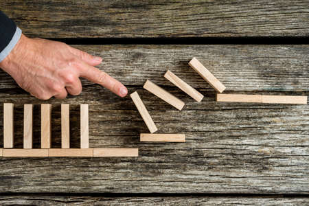 Solution concept with business man demonstrating stopping the domino effect using wooden bricks. Stock Photo