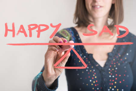 Happy - Sad balance concept with a woman drawing a seesaw with chalk on a virtual screen.