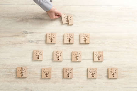 Bright ideas, creative thinking and success in a conceptual image of light bulbs drawn on wooden blocks forming a pyramid with a businessman completing the last block in the apex. Stock fotó
