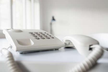 古典的な白い固定電話受話器低角度表示、オフィスの机の上。