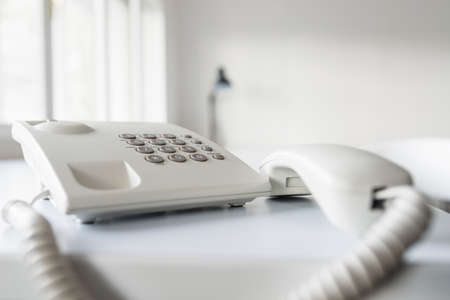 Classical white landline telephone with receiver off the hook on an office desk, low angle view. Stock Photo