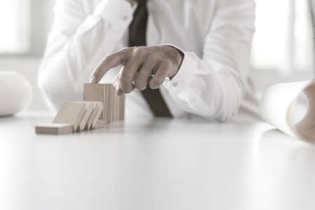 Man preventing dominoes from crumbling on a white office table, retro effect faded look.