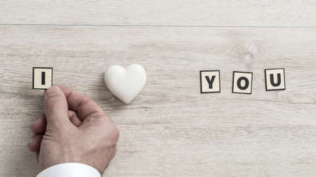 I Love You message with the hand of a man placing a letter to represent Love on a wooden background.