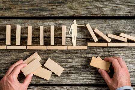 Conceptual close-up of the hands of a man building a stable bridge or a structure for a paper man stopping the collapse of wooden blocks.
