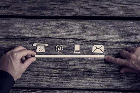 電話、ウェブサイト、素朴な大まかなウッドの背景に実業家の手によってサポートされている行内メール アイコンとコミュニケーション ・ コンセ