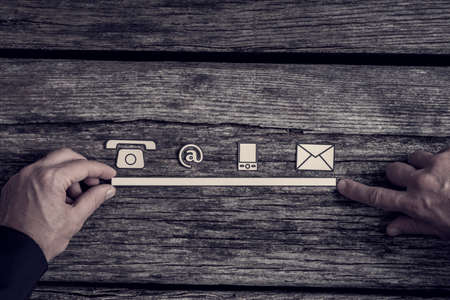 Communications concept with phone, website, and mail icons in a row supported by the hands of a businessman over a rustic rough wood background.