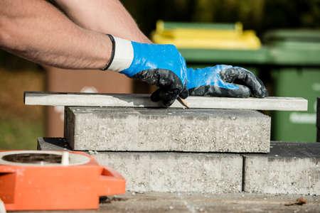 Bouwer die een straatsteen of blok markeert om te snijden terwijl hij een nieuwe vloer legt in een close-up van zijn gehandschoende handen.