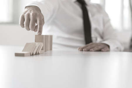 Close up view on hand of business man stopping falling blocks on office  table for concept about management.