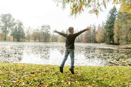 Young boy jumping for joy with outstretched arms as he celebrates the tranquility of an autumn landscape with lake and fallen leaves on the grass, with lateral copy space.