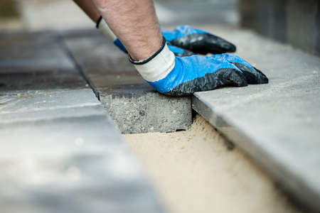 Builder laying new paving bricks or stones placing them in position on a foundation of levelled ands in a close up view of his gloved hands.