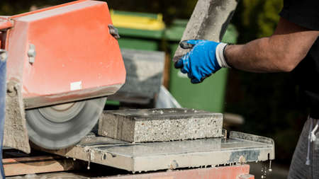 Building contractor working with a concrete block and an angle grinder, closeup view of his hands and the power tool.