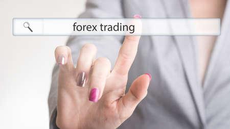 彼女はさらなる情報を求めるように透明な仮想画面上で外国為替取引という言葉でウェブ検索バーに触れる女性の手。