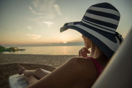 Single woman looking at sunset sitting on a chair on the beach.