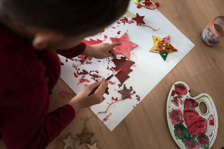 Toddler painting wooden decorations red on a sheet of paper kneeling on the floor. Фото со стока