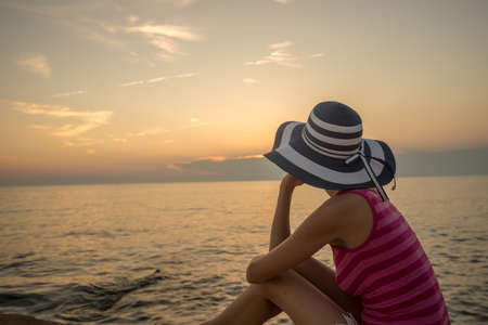 View from behind of a woman wearing striped pink shirt and blue straw hat looking at the sunset over sea.