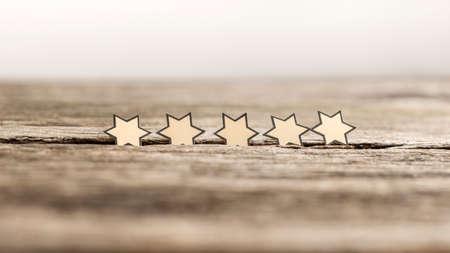 Vijf sterren op een rij op rustieke houten planken. Conceptueel van uitstekende mening.