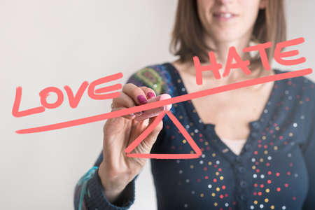 Conceptual image of a woman drawing a seesaw showing an imbalance between word Love being weighted more than the word Hate on opposites ends. Stok Fotoğraf
