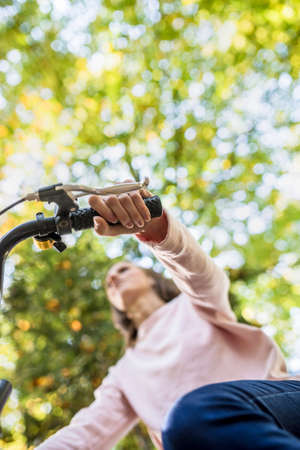 Woman riding a bicycle viewed from below focus at her hand on the handle bars against leafy green trees. Stock Photo