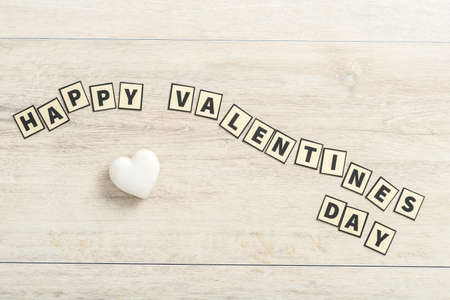 Happy valentines day concept spelled out with rectangular letters in a wavy line over a wooden background with a heart ornament. Stock fotó