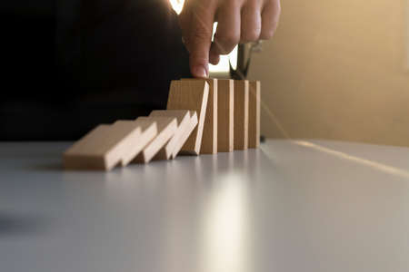 Closeup of a businessman stopping domino effect with his finger at sunset. Stock Photo