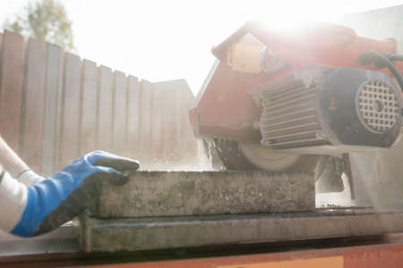 Close up view of a building contractor using an angle grinder or circular saw outdoors to cut through a paving slab or brick in a cloud of dust.