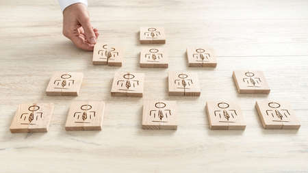 Human resources concept with a businessman arranging a series of wooden blocks depicting people into a pyramid.