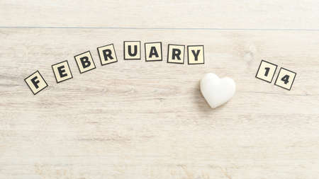 February 14 spelled out with rectangular letters over a wooden background with a small white heart ornament.