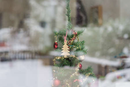 Christmas tree decorated with seasonal ornaments viewed through a glass window with reflections of the snow and garden outside. Stock Photo
