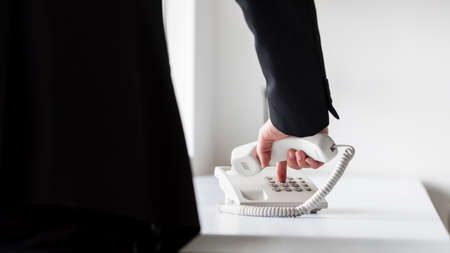 Businessman dialing telephone number on a classical white landline telephone, low angle view between his arm and body. Banco de Imagens