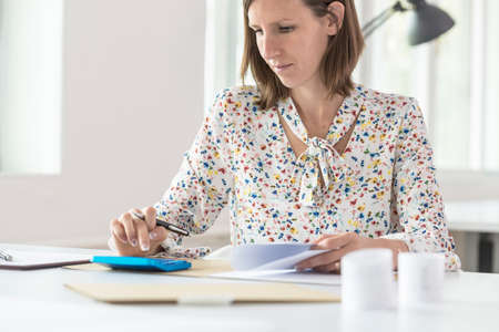 Front view of female accountant doing a calculation on a blue manual calculator. Stock Photo