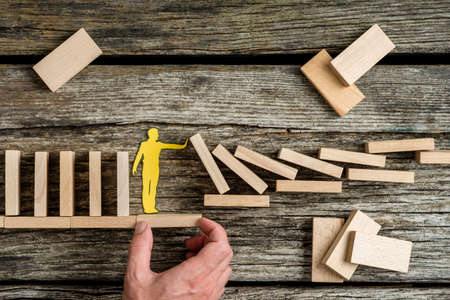 Conceptual close-up of the hand of a man offering support through a stable platform to a paper man stopping the collapse caused by domino effect.