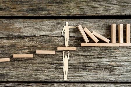 나무 블록의 부정적인 도미노 효과를 중지하는 동안 지원으로 다른 사람을 돕는 종이 남자의 실루엣의 개념적 근접.