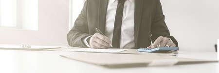 Accountant schrijven van notities en werken met een handmatige rekenmachine op zijn boeken balanceren in een lage hoek uitzicht over het bureau.