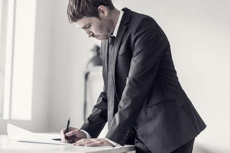Zijaanzicht van een ontwerper of tekenaar met behulp van liniaal en potlood tijdens het werken aan het plan van een moeilijk project op kantoor, afgezwakt retro-effect.