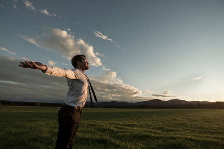 Businessman celebrating a new day standing in his shirt with outstretched arms in a rural field as the sun peeps over the distant mountains. Stock Photo