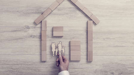 Man placing a cut out of his family inside a wood frame home in a concept of home ownership over a wooden background, toned retro effect. Reklamní fotografie