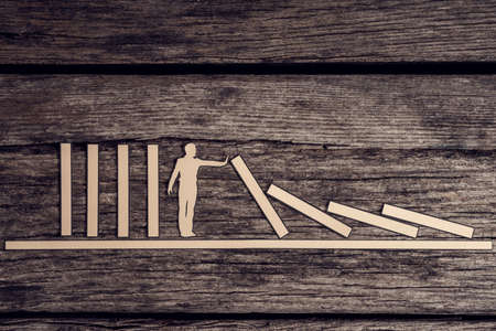 Retro image of stopping the domino effect concept with paper cutout of a man preventing a line of dominoes from falling over a rustic wood background.