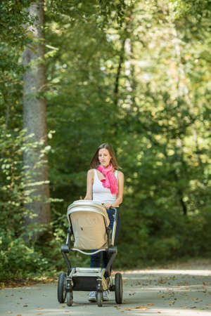 Attractive stylish woman pushing a baby stroller along a rural road through leafy green trees.