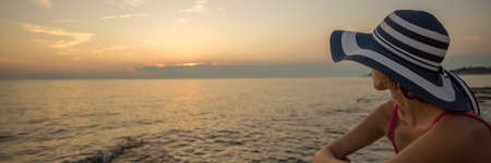 Wide panorama view of woman in pink sleeveless shirt and sunhat watching sunset over sea, copy space.