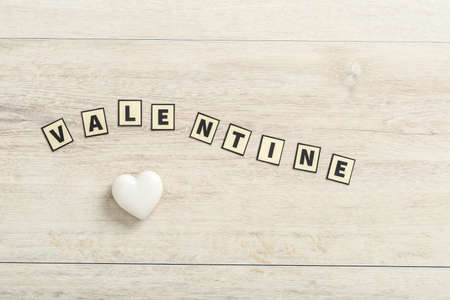 Valentine spelled out with rectangular letters over a wooden background with a small white heart made of stone.