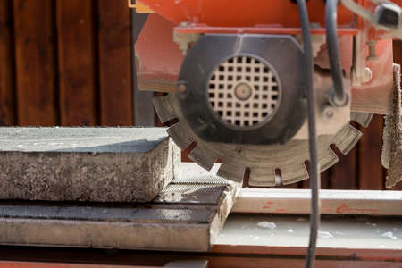 Concrete block and an angle grinder outdoors in a construction concept.
