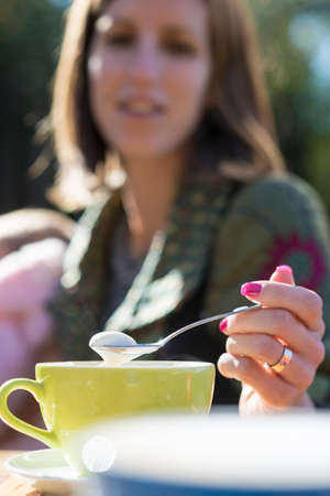 Young woman  with varnished nails spooning froth on a coffee as she sits outdoors in the sunshine in a close up view of the spoon across the table.