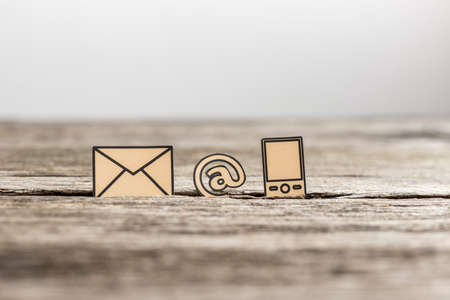 Business communications concept with three icons for email, a web address and telephone on textured rustic wooden table.