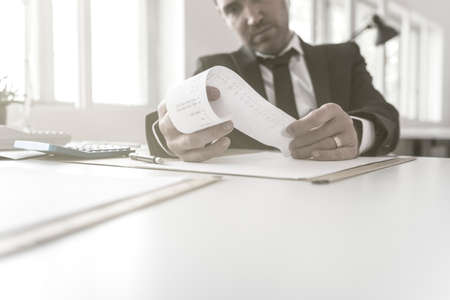 Businessman or accountant checking a printout off an adding machine or till receipt as he sits at his desk in a low angle cropped view. Stock Photo