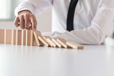 Businessman in white shirt stopping domino effect. Stability concept. Stockfoto