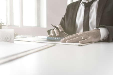 Accountant die aan zijn rekeningen werkt die blauwe calculator in close-upmening gebruiken van zijn handen.