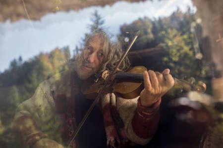 ガラスの窓の後ろでバイオリンやフィドルを演奏するシニア男性バイオリニスト。
