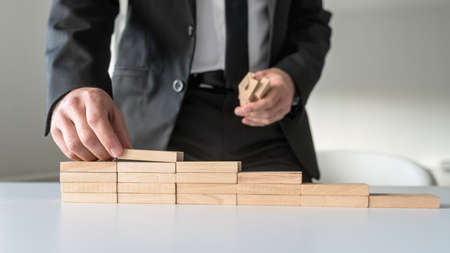 Front closeup view of businessman standing behind his office desk constructing steps of wooden pegs.