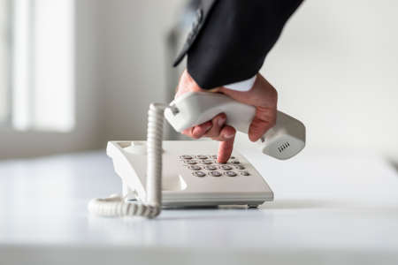 Male hand dialing a telephone number in order to make a phone call on a classical white landline telephone.