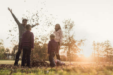 Young family playing with autumn leaves standing in a circle in nature tossing them into the air and laughing, retro effect faded look.